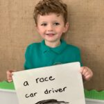 A child holding up a board showing their ambition for later life